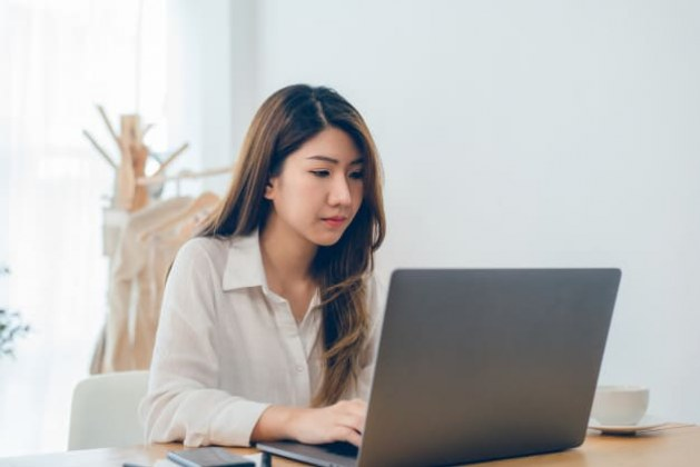 beautiful-young-smiling-asian-woman-working-laptop-while-home-office-work-space_7861-914
