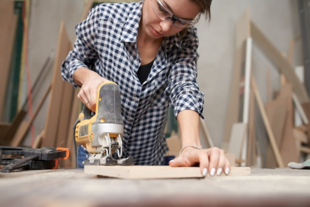 woman-carpenter-working-with-fretsaw-workshop
